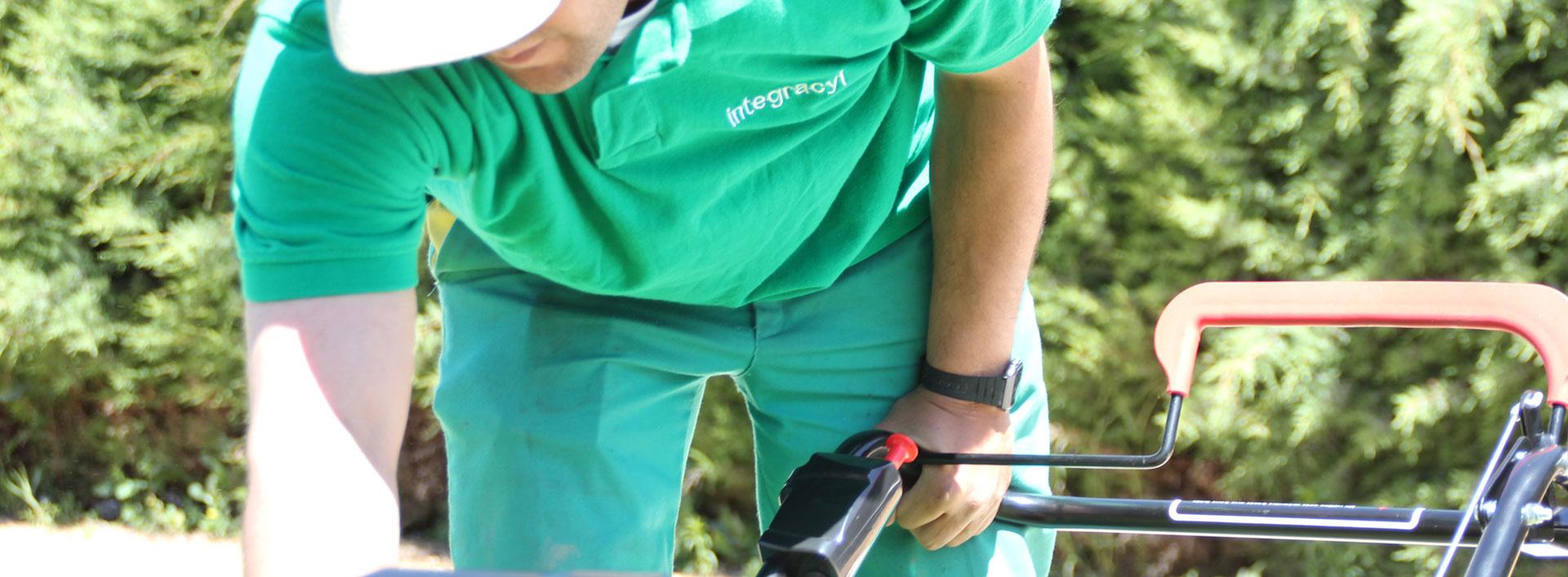Trabajador de Integracyl, jardinero activando una máquina cortacésped